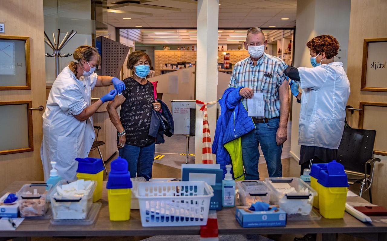 Liz en Dennis Stijger krijgen de griepspuit van assistentes van de huisartsenpraktijk Kroijenga & De Jong in Workum.