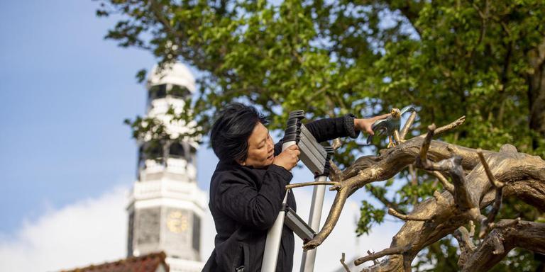 Kunstenares Shen Yuan plaatst in Hindeloopen nog wat vogeltjes in de bomen van haar fontein.