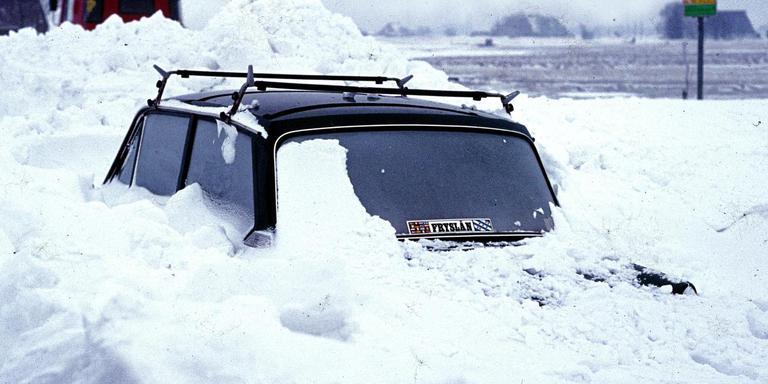 Een ingesneeuwde auto. Gelukkig is de bushalte dichtbij, hoewel het de vraag is of de bus hier nog kan komen. FOTO HENK BOOTSMA