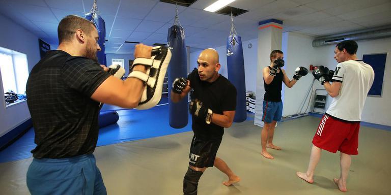 Nihad Solunovic (links) traint Alexander, Jamie en Wesley (van links naar rechts) in zijn vechtsportschool.