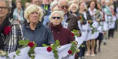 Nabestaanden van geweldsslachtoffers dragen een lint met daarop de namen van hun naasten.