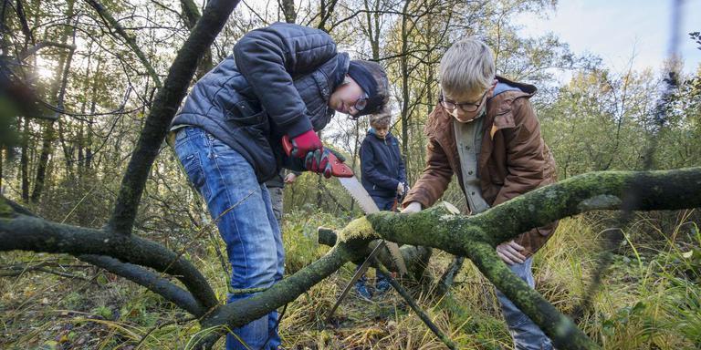 Teun Stegeman (links) en Mick Lenstra uit Heerenveen helpen een handje op de Natuurwerkdag. FOTO RENS HOOYENGA