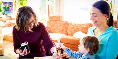 Femke Nijboer (links) op bezoek bij Ineke Geelen en haar zoontje Jacy om te helpen met het papierwerk voor de peuteropvang. FOTO JILMER POSTMA