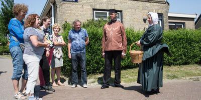 Jeanette Nobel de Jong en haar man Pieter Nobel liepen dit weekeinde, gehuld in achttiende-eeuwse Amelander klederdracht, al vertellend door Buren in het het kader van het Verhalenfestival. Hier staan ze voor het voormalige zuivelfabriekje van Buren. FOTO JAN SPOELSTRA