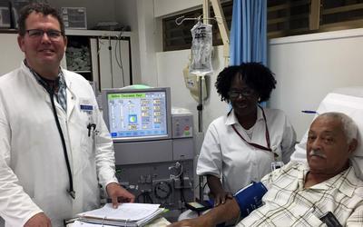 Gabe van Essen (links) in het Sint Maarten Medical Center, met Anita Rotsburg, hoofdverantwoordelijke dialyse-afdeling, en een patiënt. FOTO GABE VAN ESSEN