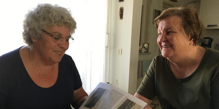 Annelies van der Geest (links) en Reina Bakker bladeren in het archief van Reina's man, Eddy Bakker. FOTO LC