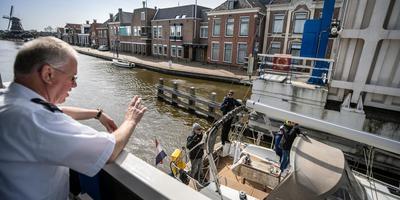 Brugwachter Jan Zijsling zwaait naar de bemanning van een schip dat door Woudsend vaart. FOTO NIELS DE VRIES