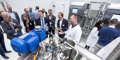 Theo Stellingwerf (in witte jas) legt onder meer gedeputeerde Johannes Kramer (zesde van links) uit wat er in het Food Application Centre for Technology gebeurt. FOTO HOGE NOORDEN/JACOB VAN ESSEN
