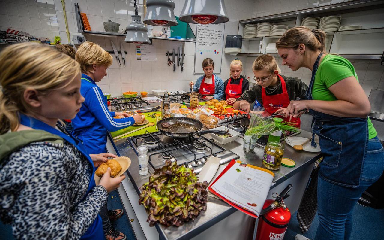 In de keuken van wijkcentrum De As in Heerenveen bereiden kinderen hun eigen maaltijd: wortelsalade en een broodje zelfgemaakte hamburger.