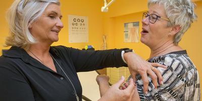 """Praktijkassistent Marjon van den Hurk geeft de griepprik aan collega Aukje Mulder in Gezondheidscentrum Oosterwolde. ,,We doen dit voor de mensen met wie we omgaan."""""""