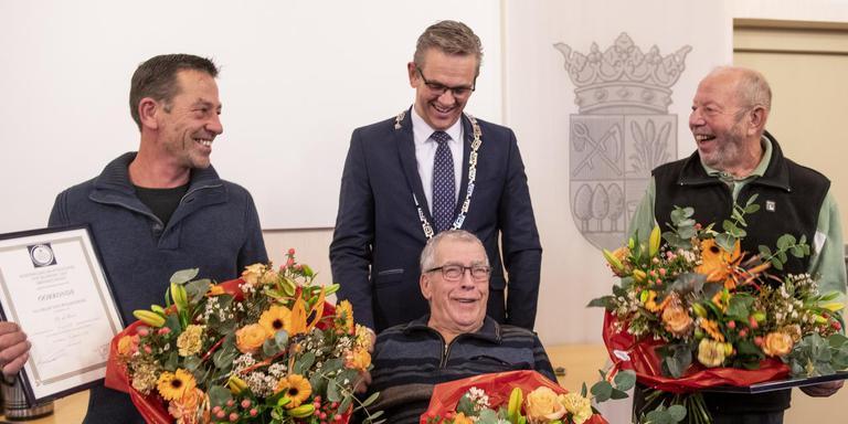Helemaal links Douwe de Bruin, helemaal rechts Gérard Kroese. In het midden burgemeester Jeroen Gebben van Tytsjerksteradiel met onder hem Gosse Hiemstra (74), die gered werd van de verdrinkingsdood. FOTO HOGE NOORDEN/JACOB VAN ESSEN
