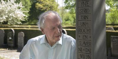 Jack Kooistra bij een oorlogsgraf op de Huizumer Begraafplaats. ,,De zware misdadigers van de SD en de SS zijn de dans ontsprongen.''