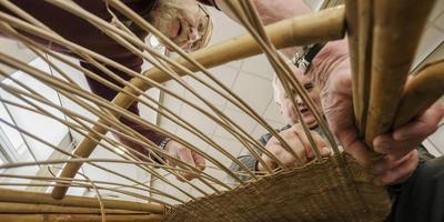 Henk Marks (rechts) wordt bij het riet vlechten geholpen door Kees Landkroon. FOTO RENS HOOYENGA