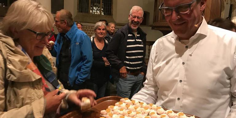 Algemeen directeur Rimmert de Jong van Koninklijke Steensma deelt in de Martinikerk in Franeker klassiek oranjekoek van banketbakkerij Schaafsma uit.