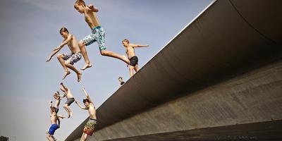 Brugspringen was de afgelopen zomer populair bij de jeugd om verkoeling te zoeken, zo ook bij Woudsend. FOTO NIELS DE VRIES
