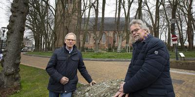 Lubbert Tilma (links) en Cees Vos bij de Sint Vituskerk in Stiens. Van de 120 bomen moeten er 30 gekapt worden. FOTO HOGE NOORDEN/JAAP SCHAAF