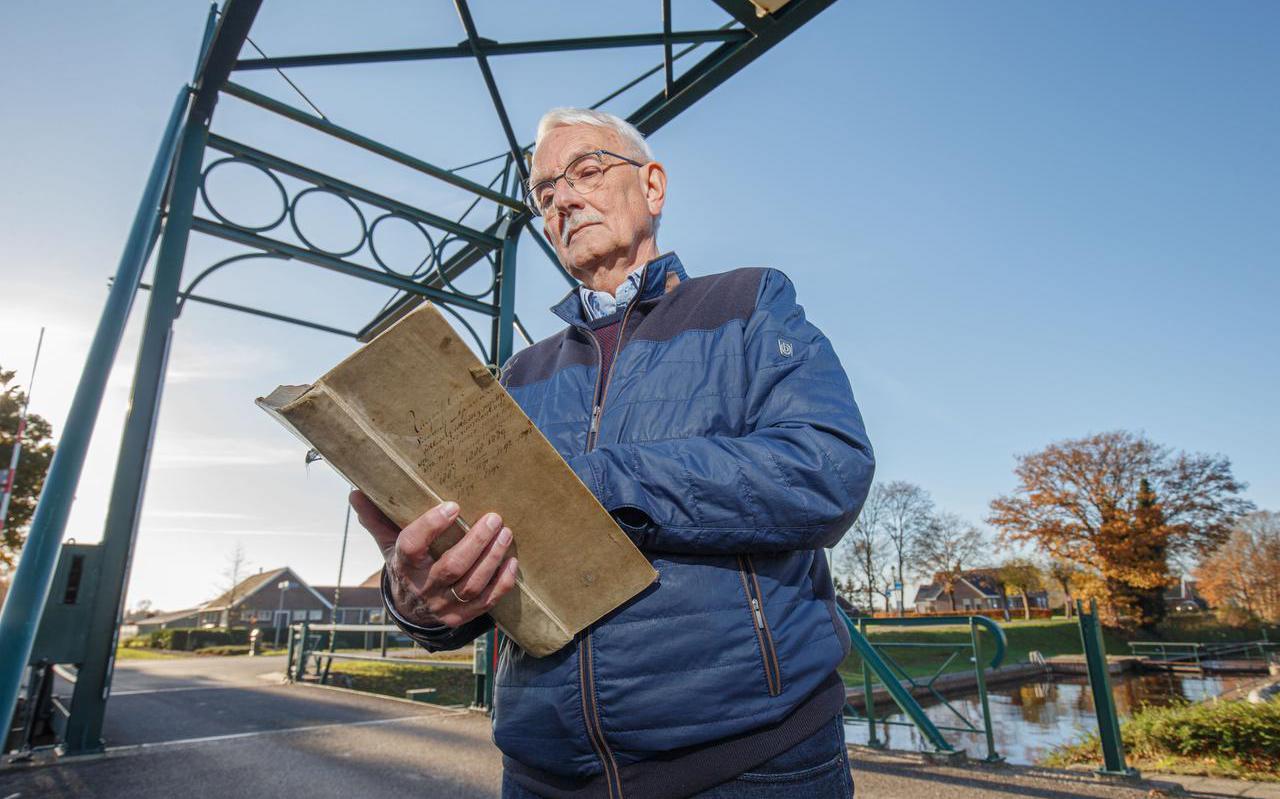 Reitze Jonkman bladert door het Uitgavenboek, op de brug over de vaart in Appelscha.