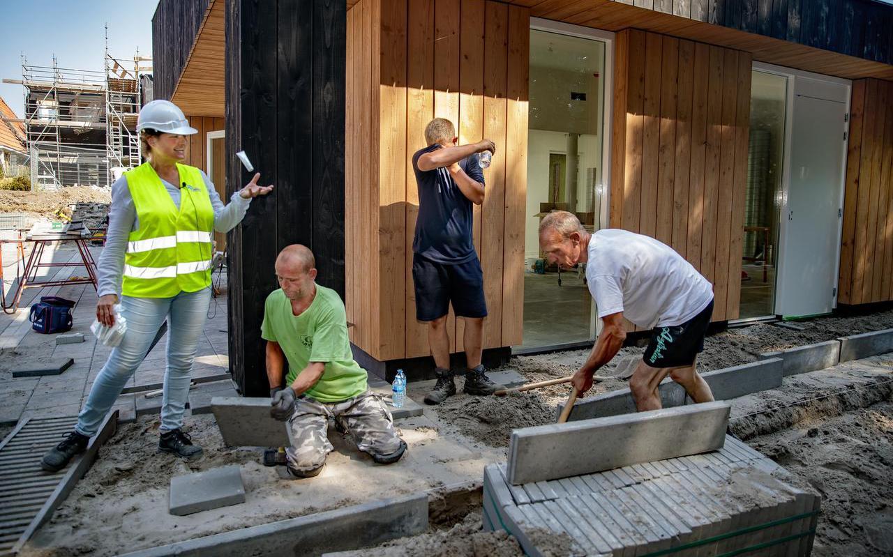 FNV-consulente Rita Minnes deelt water uit aan bouwvakkers in de nieuwbouwwijk Houkepoort in Sneek. FOTO NIELS DE VRIES