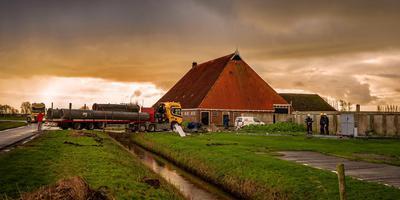 Een dieplader voert de restanten af van de omgevallen windmolen op het erf van Jan van der Hem in Jorwert.