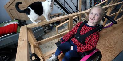 Luna Wassenaar uit Leeuwarden poseert met haar poes Lieffie. De achtjarige heeft de zeldzame Noordzeeziekte en gaat snel achteruit. Haar roze rollator heeft plaatsgemaakt voor een roze rolstoel.