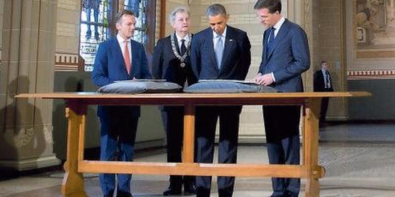Voormalig president Obama kreegt het Plakkaat van Verlatinghe te zien tijdens zijn bezoek aan Nederland in 2014. FOTO AFP.
