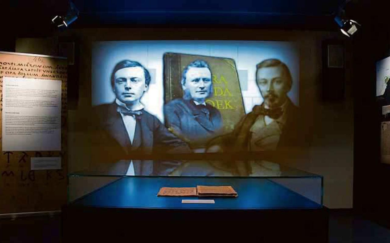 François HaverSchmidt, Cornelis over de Linde en Eelco Verwijs, op een projectie achter de vitrine met het Oera Lindaboek bij Tresoar in Leeuwarden. FOTO LC/ASING WALTHAUS