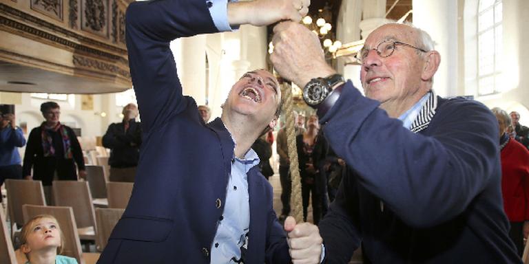Sander de Rouwe (links) en Henk Kroes trekken - aanvankelijk vergeefs - aan het symbolische klokkentouw. FOTO NIELS WESTRA.