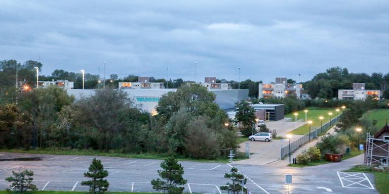De deels verscholen Waddenhal gezien vanaf de Westerzeedijk. Links de velden van de Harlinger hockeyclub HMHC.
