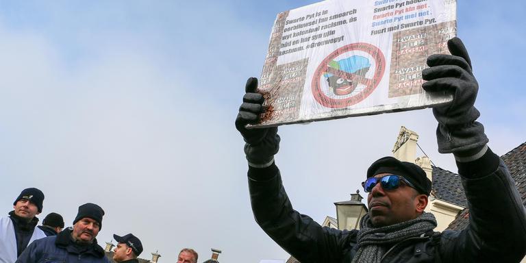 Een demonstrant houdt een bord omhoog, beveiligers kijken toe. FOTO LC/ARODI BUITENWERF