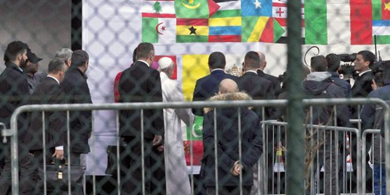Paus kust voeten van vluchtelingen