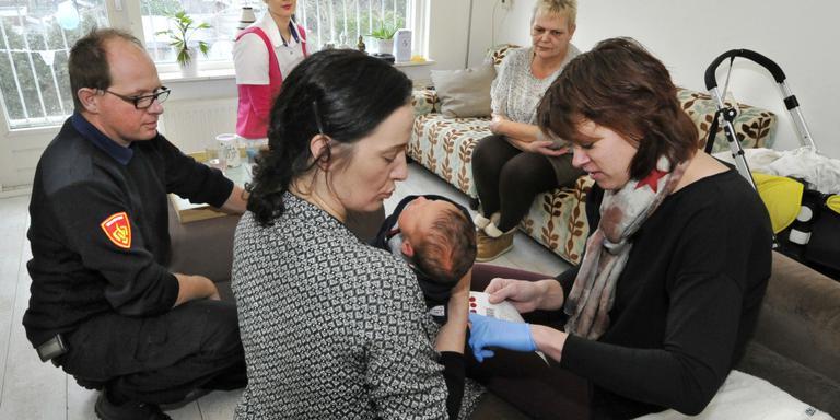 Anneke Dijkstra (rechts) geeft de pasgeboren Ilias een hielprik. FOTO LC