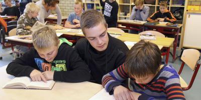 Student Laurens de Boer begeleidt 'zijn' leerlingen Cor de Vries en Lorenzo Hendriks. Op de achtergrond juf Diny Bakker. FOTO SIMON BLEEKER