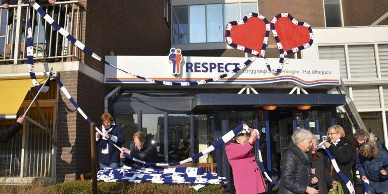Mensen van zorgcentrum Het Uiterjoon in Scheveningen omwikkelen hun gebouw met een kilometerslange Friese sjaal. FOTO MARIANNE QUISPEL