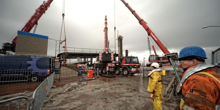 Werkmannen Henk (r) en Jan kijken toe hoe drie zware kranen het brugdeel van zijn plaats tillen. FOTO JAN SPOELSTRA
