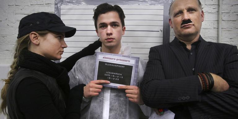 Student Wessel Peckelsen geflankeerd door 'bewakers' tijdens het nemen van zijn 'mugshot'. Foto Niels Westra
