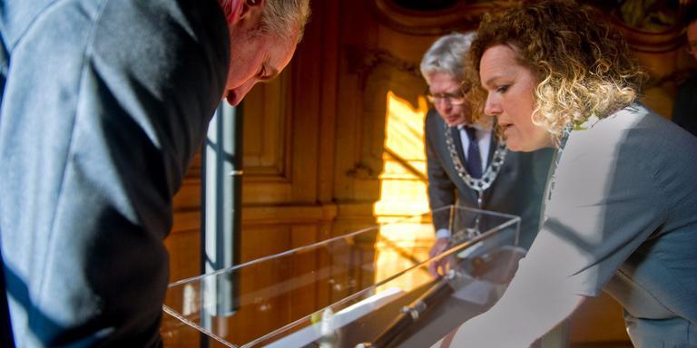 Eduard van Zuijlen, burgemeester van Franekeradeel, en Manon Borst overhandigen de pedelstaf aan Ferd Crone. FOTO HOGE NOORDEN/JACOB VAN ESSEN