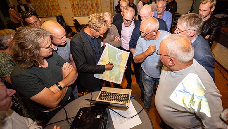 Rijkswaterstaat-morfoloog Ernst Lofvers (met kaart) bespreekt met Amelanders de morfologie van de geulen in de Waddenzee tijdens een praatavond op het eiland over de vaarverbinding. FOTO JAN SPOELSTRA.NL