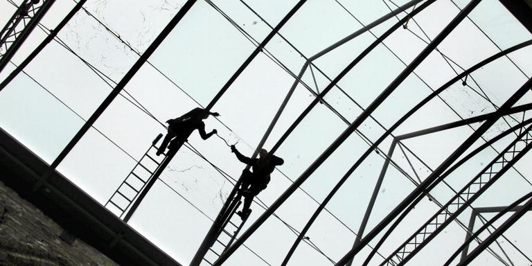 Werklui zijn bezig met het glas, tijdens een eerdere restauratie. FOTO ARCHIEF LC