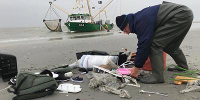 LC-verslaggever Wieberen Elverdink: ,,We proberen nu zo veel mogelijk rommel vanaf de zandplaat de kotter in te krijgen. Zware klus.'' FOTO LC