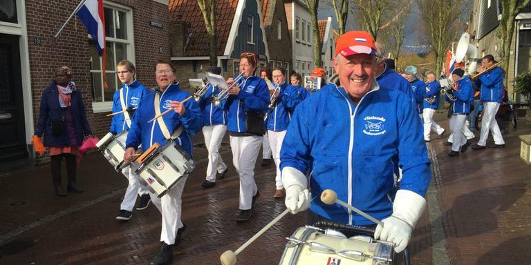 Jos Houter slaat op de trom tijdens de tocht van de drumband op Vlieland.