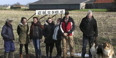 Verontruste omwonenden bij een door hen geplaatst protestbord tegen de komst van het azc. Foto Simon Bleeker
