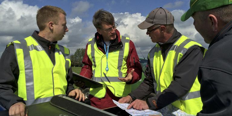 Van links naar rechts Roelf Tienstra, examinator Martin Joosse, Christel Thijssen en Gosse Wouda. Ze besturen een kaart van het gebied.