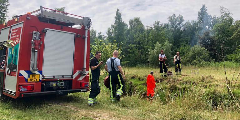 Het vuur is lastig te bereiken. Brandweerlieden moeten blusapparatuur door een slootje overbrengen naar het eilandje. FOTO JARING RISPENS