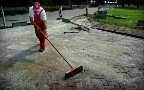 Een stratenmaker veegt zijn pas gelegde straat schoon.