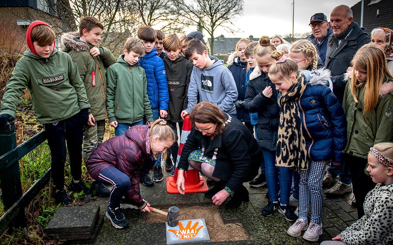 Samen met burgemeester Ellen van Selm legt de tienjarige Maxine Veenstra de eerste zwaaisteen van Opsterland in de Kuiperstraat in Beetsterzwaag.