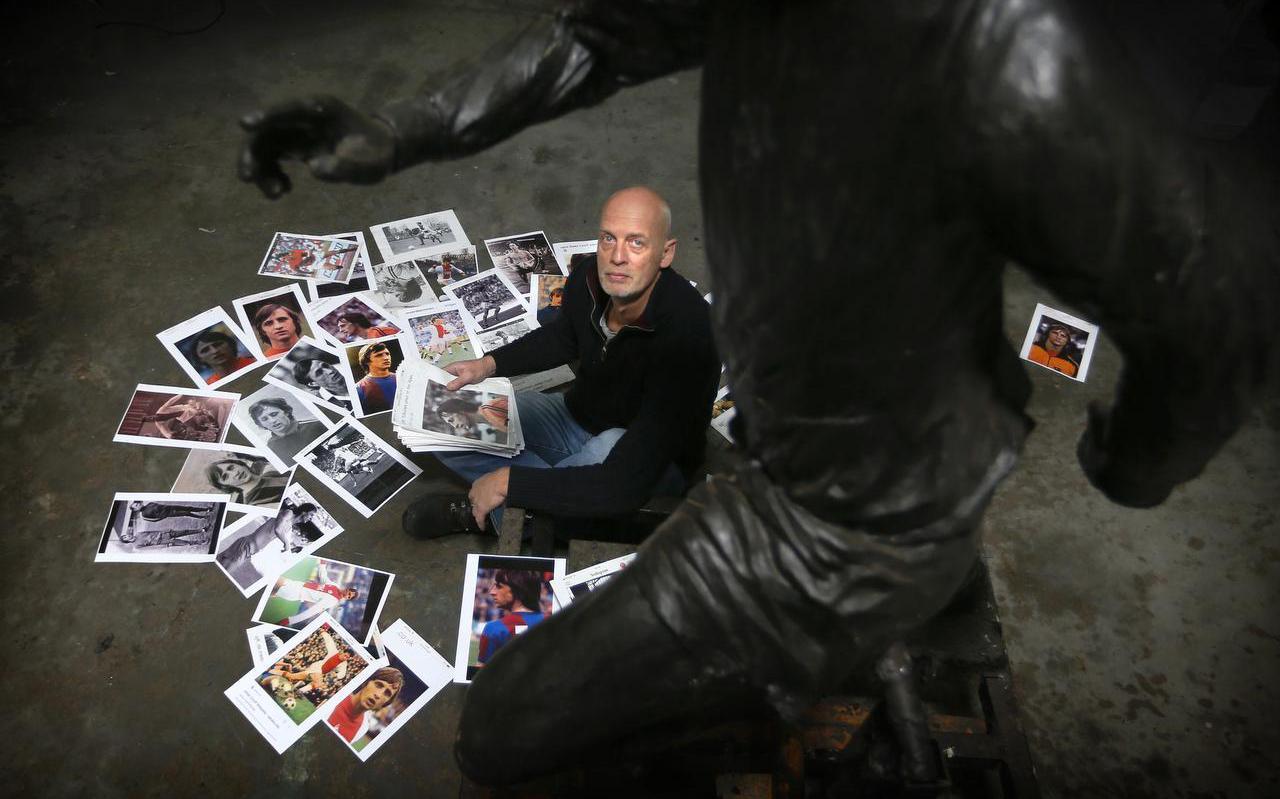 Hans Jouta bij het beeld dat hij maakte van Johan Cruijff.