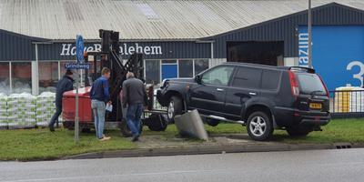De auto wordt met een heftruck weer op de banden gezet. FOTO ANTON KAPPERS