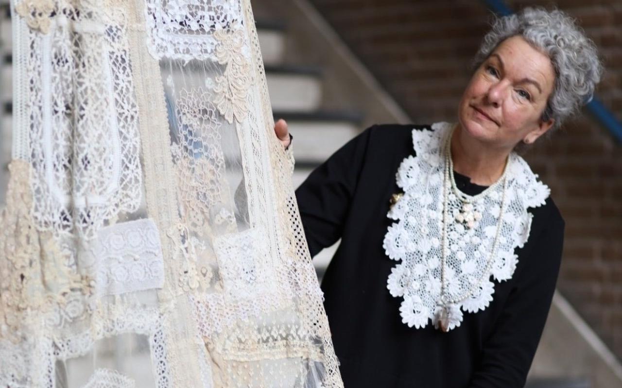 Ellis Schoonhoven toont in de hal van DOAS een deel van de sluier nadat vrouwen uit Friesland eraan hebben gewerkt.