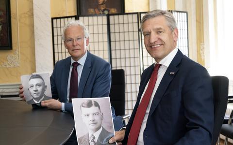 Burgemeester Sybrand Buma van Leeuwarden en burgemeester Jan Rijpstra van Smallingerland met in hun hand een foto van hun grootvaders die beiden tijdens de Tweede Wereldoorlog omkwamen in kamp Neuengamme.