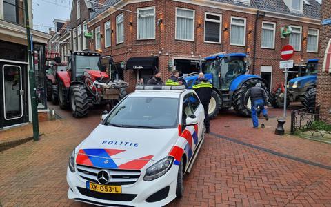 Boeren met trekkers in het centrum van Dokkum. De politie blokkeert met hun wagen een deel van de boeren.